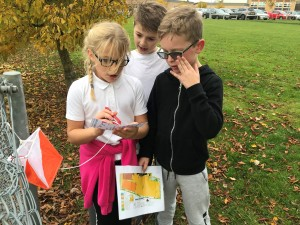 Children finding a control marker in the orienteering